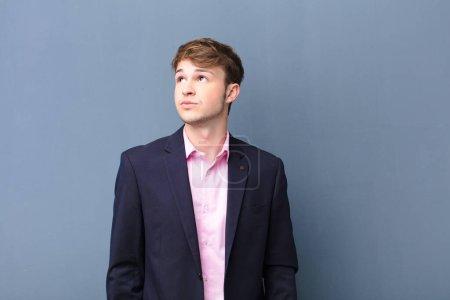 Photo pour Jeune homme blond avec une expression inquiet, confus, désemparé, levant les yeux pour copier l'espace, doutant isolé contre un mur plat - image libre de droit