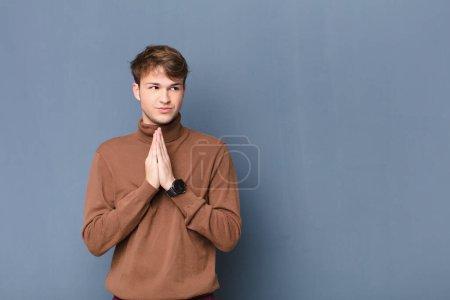 Photo pour Jeune homme blond se sentant fier, espiègle et arrogant tout en complotant un plan maléfique ou en pensant à un tour isolé contre un mur plat - image libre de droit