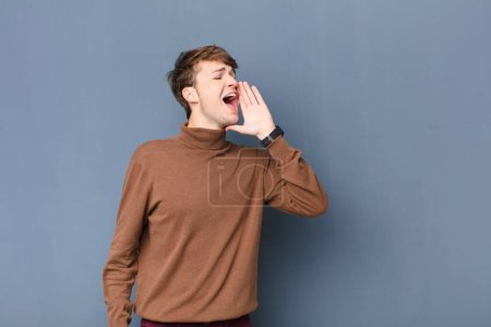 Photo for Young blonde man yelling loudly and angrily to copy space on the side, with hand next to mouth isolated against flat wall - Royalty Free Image