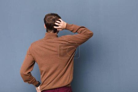 Photo pour Jeune homme blond se sentant désemparé et confus, pensant une solution, avec la main sur la hanche et d'autres sur la tête, vue arrière isolée contre un mur plat - image libre de droit