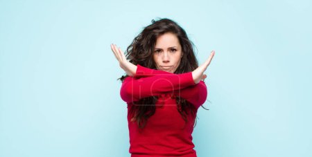 Photo for Young pretty woman looking annoyed and sick of your attitude, saying enough! hands crossed up front, telling you to stop against blue wall - Royalty Free Image
