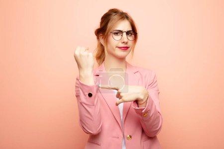 Foto de Joven mujer rubia bonita mirando impaciente y enojado, apuntando a reloj, pidiendo puntualidad, quiere llegar a tiempo. concepto de negocio - Imagen libre de derechos