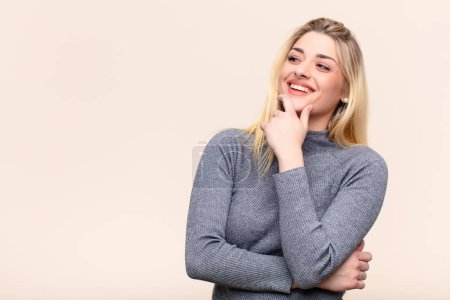 Photo for Young pretty blonde woman smiling with a happy, confident expression with hand on chin, wondering and looking to the side against flat wall - Royalty Free Image