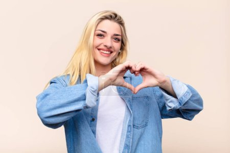 Photo pour Jeune jolie femme blonde souriante et se sentant heureuse, mignonne, romantique et amoureuse, ce qui rend la forme du cœur avec les deux mains contre un mur plat - image libre de droit