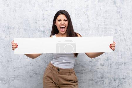 Photo pour Jeune jolie femme tenant une bannière contre le mur grunge - image libre de droit