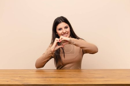 Photo pour Jeune jolie femme souriante et se sentant heureuse, mignonne, romantique et amoureuse, faisant forme de coeur avec les deux mains assises à une table - image libre de droit