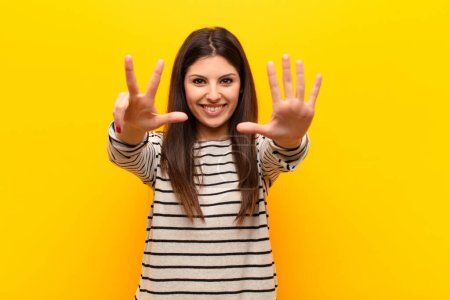 Photo for Young pretty woman smiling and looking friendly, showing number eight or eighth with hand forward, counting down against yellow wall - Royalty Free Image