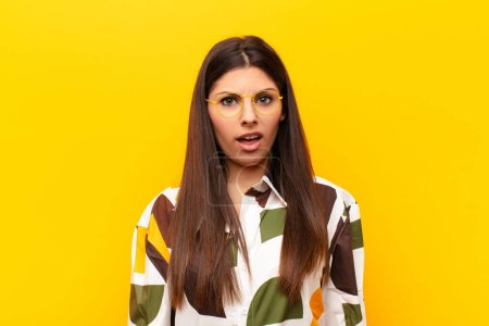 Photo for Young pretty woman feeling puzzled and confused, with a dumb, stunned expression looking at something unexpected against yellow wall - Royalty Free Image