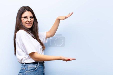 Photo pour Jeune jolie femme tenant un objet avec les deux mains sur le côté copier l'espace, montrant, offrant ou annonçant un objet - image libre de droit