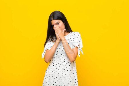 Photo for Young pretty latin woman feeling worried, hopeful and religious, praying faithfully with palms pressed, begging forgiveness against flat wall - Royalty Free Image