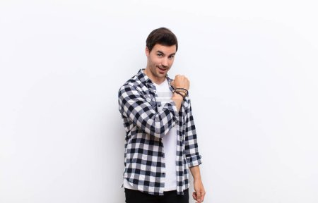 Photo for Young handsome man feeling happy, positive and successful, motivated when facing a challenge or celebrating good results against white wall - Royalty Free Image