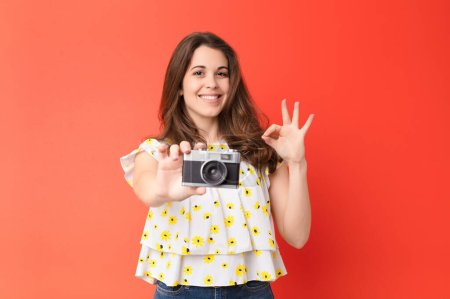 Photo for Young pretty woman with a vintage camera against red wall - Royalty Free Image