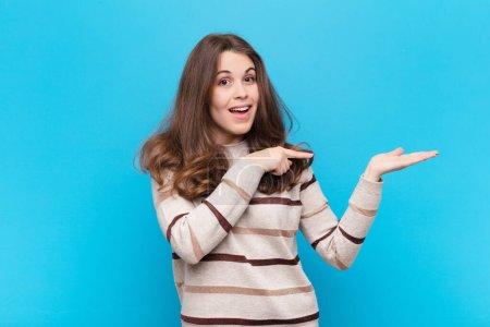 Photo pour Jeune jolie femme souriant joyeusement et pointant vers copier l'espace sur la paume sur le côté, montrant ou annonçant un objet contre le mur bleu - image libre de droit
