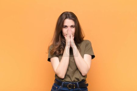 Photo pour Jeune jolie femme se sentant inquiète, pleine d'espoir et religieuse, priant fidèlement avec les paumes pressées, demandant pardon contre le mur orange - image libre de droit