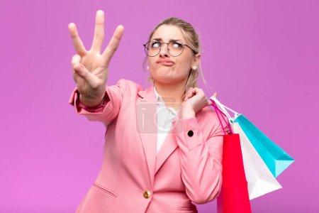 Photo pour Jeune jolie femme blonde tenant des sacs à provisions - image libre de droit
