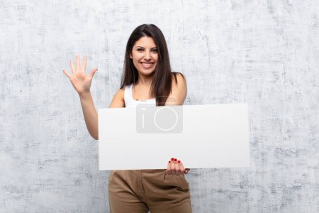 Photo for Young pretty woman holding a banner against grunge wall - Royalty Free Image