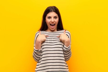 Photo for Young pretty woman feeling happy, surprised and proud, pointing to self with an excited, amazed look against yellow wall - Royalty Free Image