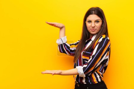 Photo pour Jeune jolie femme tenant un objet avec les deux mains sur le côté copier l'espace, montrant, offrant ou annonçant un objet contre le mur jaune - image libre de droit