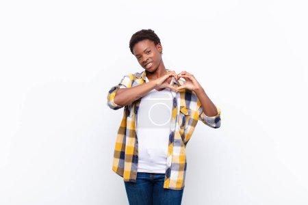 Photo pour Les jeunes jolies femmes noiressouriant et se sentant heureux, mignon, romantique et amoureux, ce qui rend la forme du cœur avec les deux mains - image libre de droit
