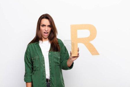 jeune jolie femme en colère, en colère, en désaccord, tenant la lettre R de l'alphabet pour former un mot ou une phrase .