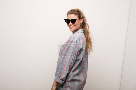 Photo for Young latin pretty woman  against flat wall wearing sun glasses - Royalty Free Image