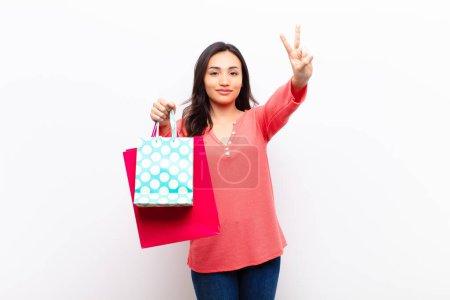 Photo pour Jeune latine jolie femme contre mur plat avec des sacs à provisions - image libre de droit