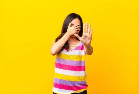 Photo pour Jeune latino jolie femme couvrant le visage avec la main et mettant l'autre main à l'avant pour arrêter la caméra, refusant des photos ou des images contre un mur plat - image libre de droit