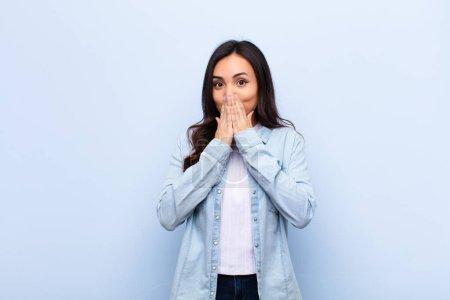 Photo pour Jeune latine jolie femme heureuse et excitée, surprise et étonnée couvrant la bouche avec les mains, gloussant d'une expression mignonne contre un mur plat - image libre de droit