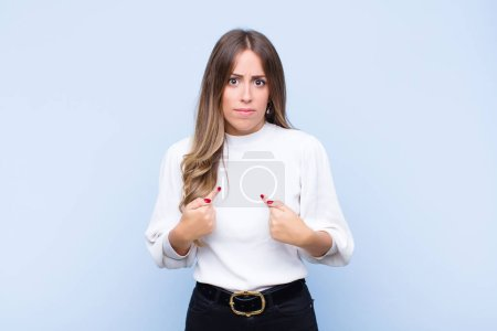 Photo for Young pretty hispanic woman pointing to self with a confused and quizzical look, shocked and surprised to be chosen against blue wall - Royalty Free Image
