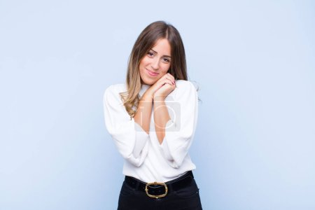 Photo for Young pretty hispanic woman feeling in love and looking cute, adorable and happy, smiling romantically with hands next to face against blue wall - Royalty Free Image