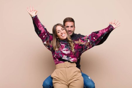 Photo for Young pretty couple against beige flat wall - Royalty Free Image