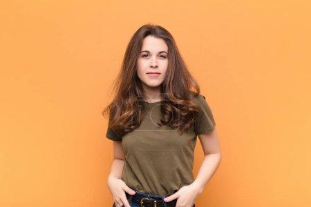 Photo pour Jeune jolie femme fière, confiante, cool, insolente et arrogante, souriante, se sentant réussie contre le mur orange - image libre de droit
