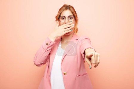 Foto de Joven mujer rubia bonita riéndose de ti, apuntando a la cámara y burlándose de ti o burlándose de ti. concepto de negocio - Imagen libre de derechos
