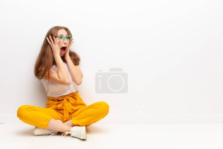 Photo for Yound blonde woman feeling happy, excited and surprised, looking to the side with both hands on face sitting on the floor - Royalty Free Image