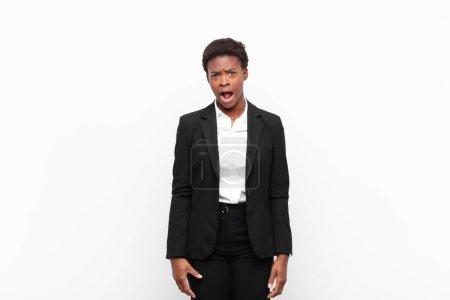 Foto de Joven bastante negro mujersintiéndose aterrorizado y sorprendido, con la boca abierta en sorpresa contra la pared blanca - Imagen libre de derechos