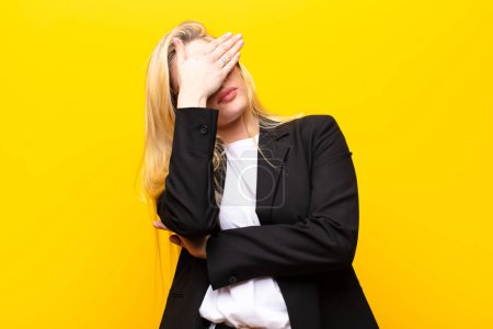 Photo for Young pretty blonde woman looking stressed, ashamed or upset, with a headache, covering face with hand against yellow wall - Royalty Free Image