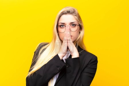 Photo for Young pretty blonde woman feeling worried, hopeful and religious, praying faithfully with palms pressed, begging forgiveness against yellow wall - Royalty Free Image