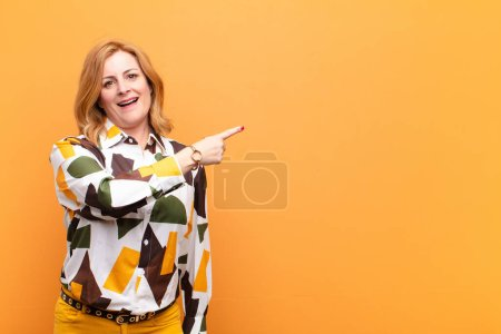 Photo for Middle age woman looking excited and surprised pointing to the side and upwards to copy space - Royalty Free Image