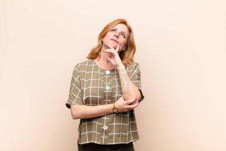 Photo pour Femme d'âge moyen se sentant réfléchie, se demandant ou imaginant des idées, rêvant et regardant vers le haut pour copier l'espace - image libre de droit