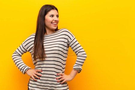 Photo pour Jeune jolie femme regardant heureux, gai et confiant, souriant fièrement et regardant de côté avec les deux mains sur les hanches contre le mur jaune - image libre de droit