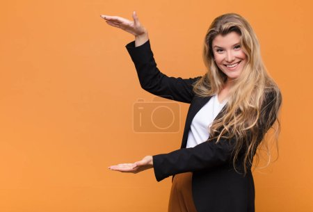 Photo for Young pretty latin woman smiling, feeling happy, positive and satisfied, holding or showing object or concept on copy space - Royalty Free Image