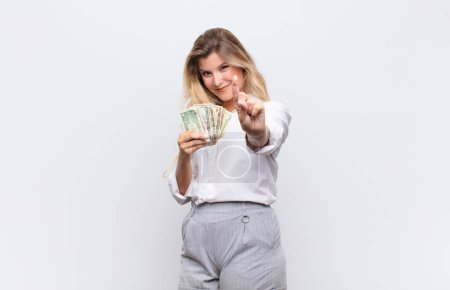 Photo pour Young pretty latin woman smiling proudly and confidently making number one pose triumphantly, feeling like a leader with dollar bills banknotes - image libre de droit