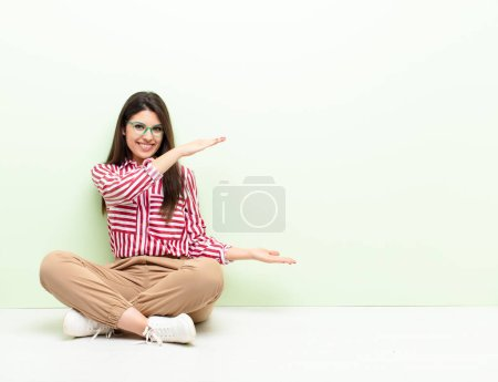Photo for Young pretty woman smiling, feeling happy, positive and satisfied, holding or showing object or concept on copy space sitting on the floor - Royalty Free Image