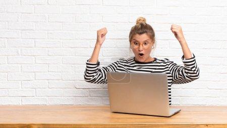 Photo pour Jeune jolie femme latine célébrant un succès incroyable comme un gagnant, l'air excité et heureux de dire prendre que ! assis avec son ordinateur portable - image libre de droit