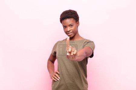 Photo pour Jeunes jolies femmes noires souriant fièrement et en toute confiance faisant la pose numéro un triomphalement, se sentant comme un leader contre le mur rose - image libre de droit