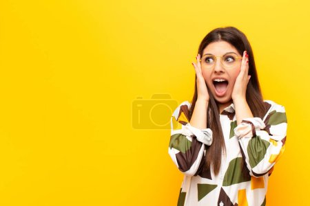 Photo for Young pretty woman feeling happy, excited and surprised, looking to the side with both hands on face against yellow wall - Royalty Free Image