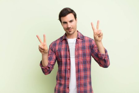Photo for Young handsome man smiling and looking happy, friendly and satisfied, gesturing victory or peace with both hands - Royalty Free Image