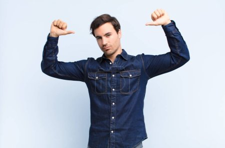 Photo for Young handsome man feeling proud, arrogant and confident, looking satisfied and successful, pointing to self against blue wall - Royalty Free Image