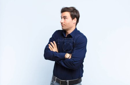Photo for Young handsome man shrugging, feeling confused and uncertain, doubting with arms crossed and puzzled look against blue wall - Royalty Free Image
