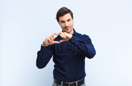 Photo for Young handsome man smiling and feeling happy, cute, romantic and in love, making heart shape with both hands against blue wall - Royalty Free Image